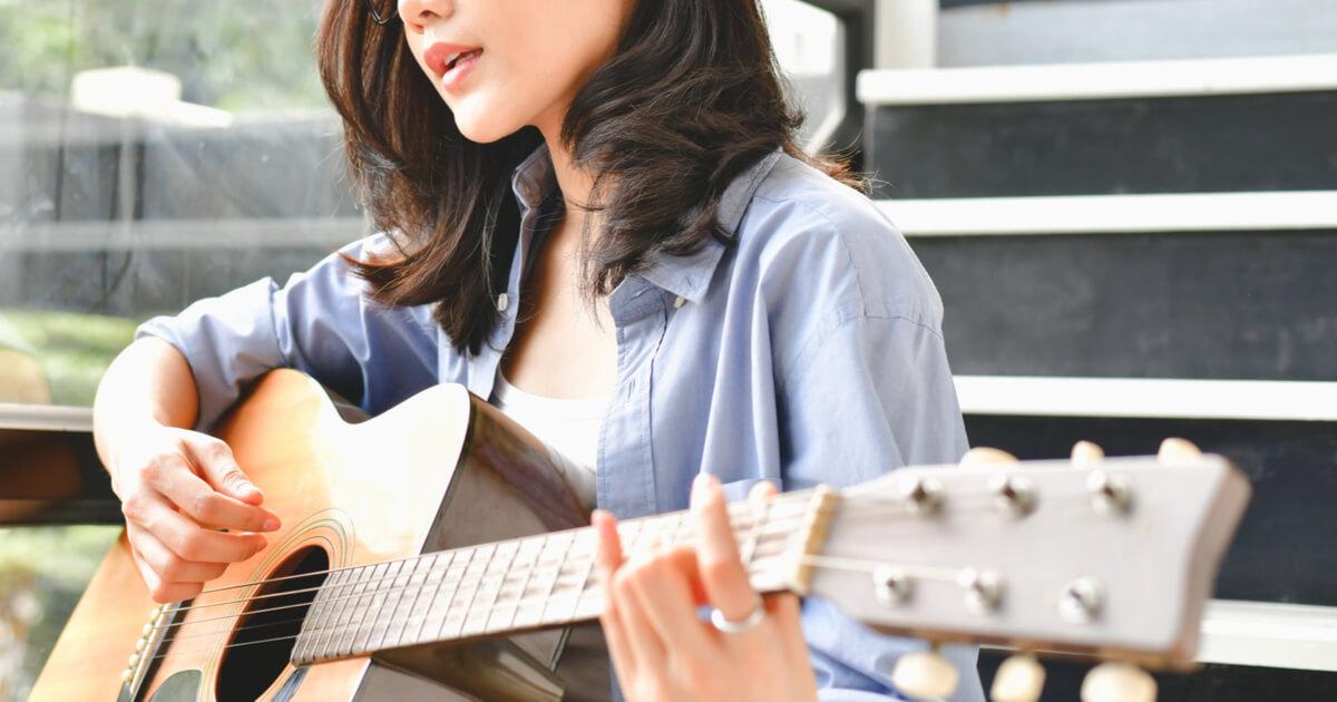 軽快にギターを弾く美女